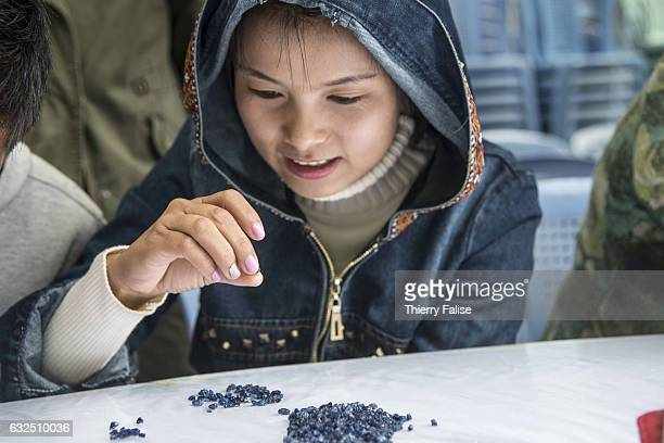 A gem buyer tests the quality of gems before a private sapphire auction organized by a mine owner