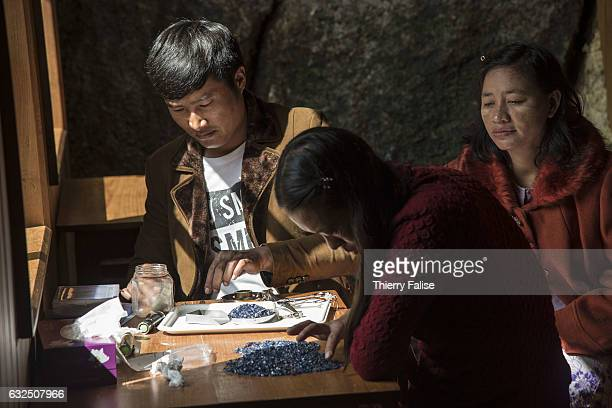 Gem buyers test the quality of gems before a private sapphire auction organized by a mine owner