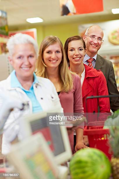 Gemany, Cologne, Man and woman waiting in supermarket, smiling