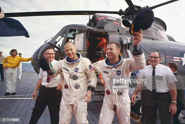 Gemini12 astronauts Buzz Aldrin and Jim Lovell wave their deck caps November 15th after leaving recovery helicopter which transported them from the...