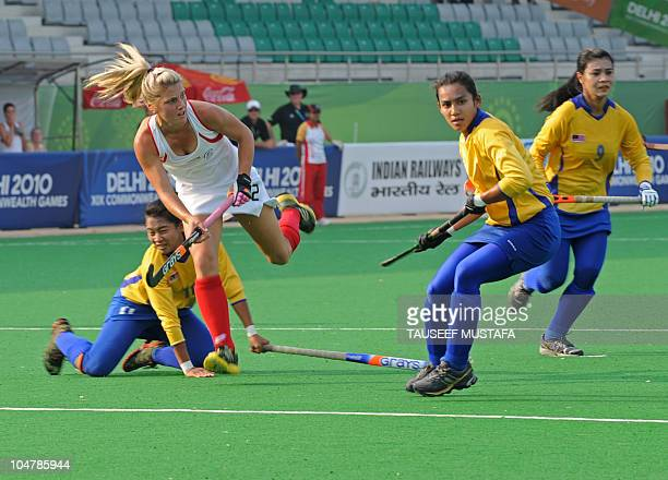 Gemma Flynn from New Zealand fights for the ball with Norhasikin Halim from Malaysia during their women's field hockey match at the Major Dhyan Chand...
