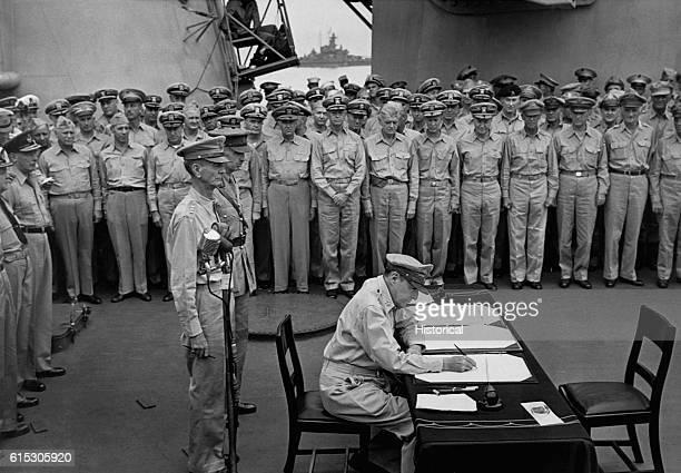 Gen Douglas MacArthur signs as Supreme Allied Commander during formal surrender ceremonies on the USSMissouriin Toyko Bay Behind Gen MacArthur are Lt...