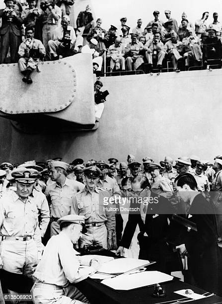 Gen Douglas MacArthur Supreme Allied Commander during formal surrender ceremonies on the USS Missouri in Toyko Bay looks on as Japan signs the...