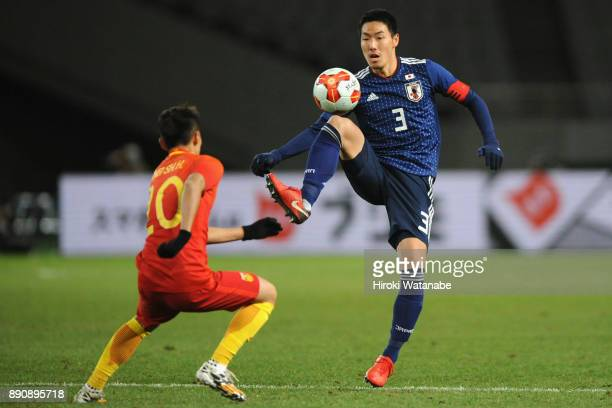 Gen Shoji of Japan and Wei Shihao of China compete for the ball during the EAFF E1 Men's Football Championship between Japan and China at Ajinomoto...