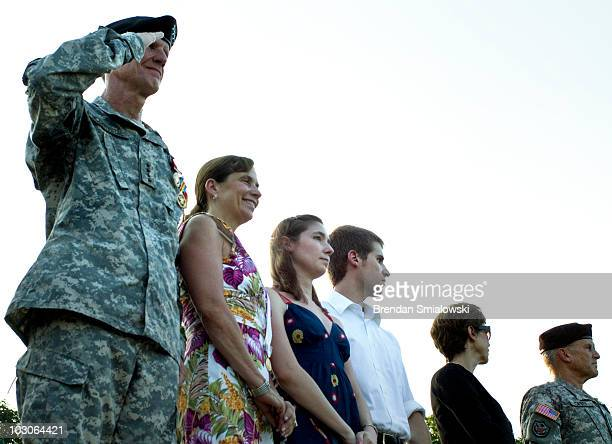 Gen Stanley McChrystal salutes while watching troops parade with his wife Annie McChrystal and others during his retirement ceremony at Fort McNair...