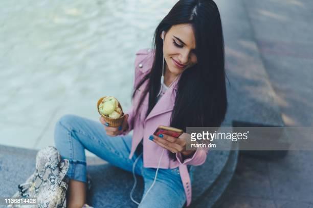 gen z chica comiendo helado y enviando mensajes de texto en el teléfono - chaqueta rosa fotografías e imágenes de stock