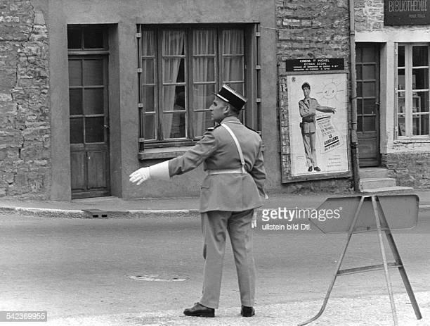 Gendarm in einem Provinzstädtchen bei der Regelung des Verkehrs im Hintergund ein Filmplakat mit Louis de Funès in 'Le Gendarme' 1965