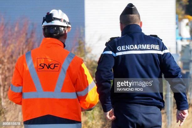 A gendarme and an employee of the National society of French railways investigate at a level crossing in Millas on December 16 two days after some...