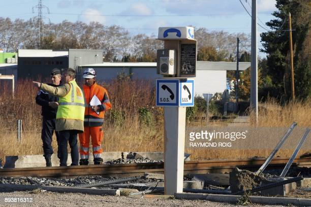 A gendarme and employees of the National society of French railways investigate at a level crossing in Millas on December 16 two days after some...