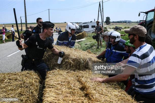 TOPSHOT A gendarme holding a baton and tear gas spray holds back protesters as other gendarmes remove haystacks from the route during a farmers'...