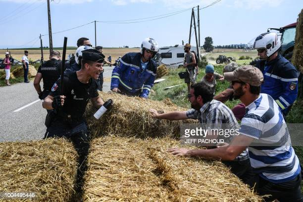 A gendarme holding a baton and tear gas spray holds back protesters as other gendarmes remove haystacks from the route during a farmers' protest who...