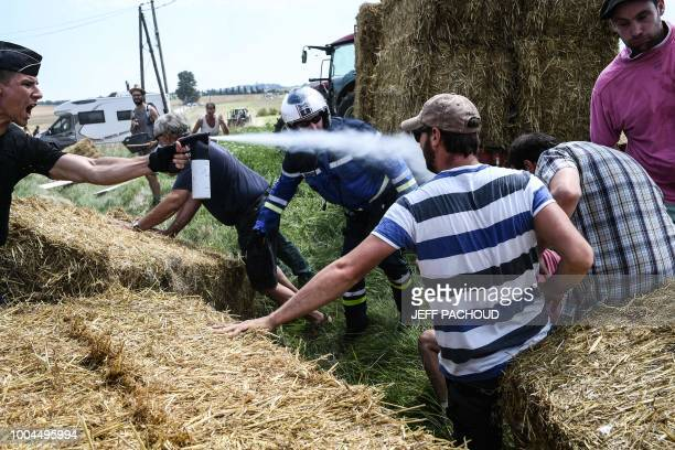 TOPSHOT A gendarme sprays tear gas at protesters as other gendarmes remove haystacks from the route during a farmers' protest who attempted to block...