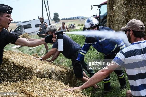 A gendarme sprays tear gas at protesters as other gendarmes remove haystacks from the route during a farmers' protest who attempted to block the...
