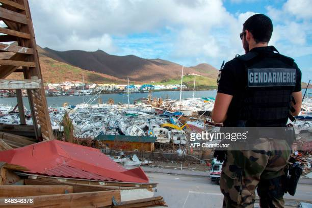 A gendarme stands in front of smashed boats on September 16 2017 at Marigot shipyard on the French Caribbean island of Saint Martin after the island...