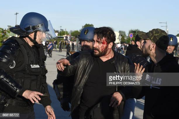 A Gendarme talks to an injured fan within clashes between Besiktas supporters and French antiriot Gendarmes outside of the Parc Olympique Lyonnais...