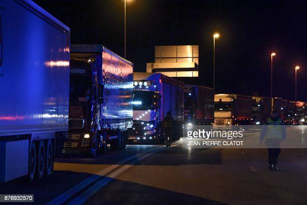 A Gendarme walks along transport trucks lined up during a blockade to access to the Frejus tunnel early on November 21 2017 close to the border...