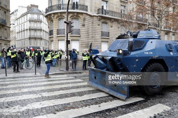 A Gendarmerie armored vehicles drives past protestors near the Champs Elysees avenue in Paris on December 8 2018 during a protest of yellow vests...