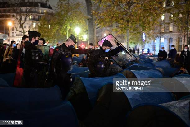 Gendarmerie forces cross Republique square to evacuate migrants and associations, after they installed tents, in Paris on November 23 one week after...