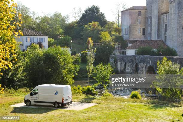 A Gendarmerie van is parked by a river searched by police divers near a house also searched by police forces in Nerac southwestern France on...
