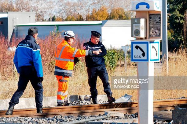 Gendarmes and an employee of the National society of French railways investigate at a level crossing in Millas on December 16 two days after some...