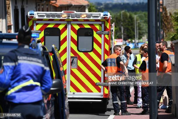 Gendarmes and emergency workers stand next to an ambulance car in which Team Ineos rider Great Britain's Christopher Froome receives medical...