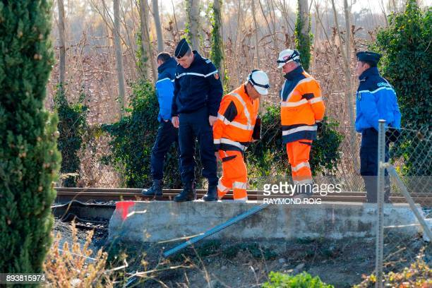 Gendarmes and employees of the National society of French railways investigate at a level crossing in Millas on December 16 two days after some...