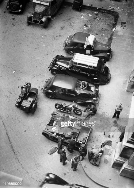 Gendarmes and FFI fighters stand near vehicles and a tank seized to German troops, in the south courtyard of Paris city hall, in August 1944, during...