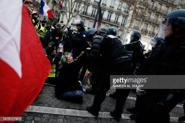 """Gendarmes attempt to remove protesters sitting in the street on the Champs-Elysees Avenue in Paris on December 29 during a """"yellow vest""""..."""