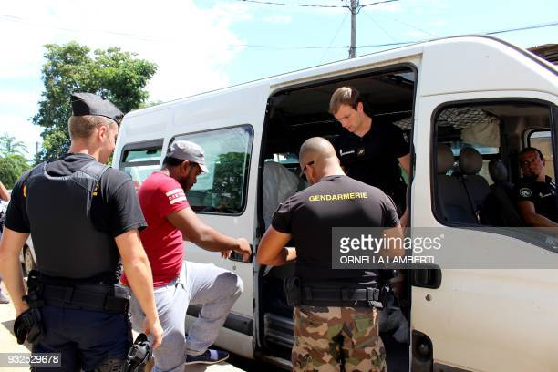 Gendarmes detain a man believed to be illegal migrant following a road control on March 15 2018 in Majicavo in the French overseas territory of...
