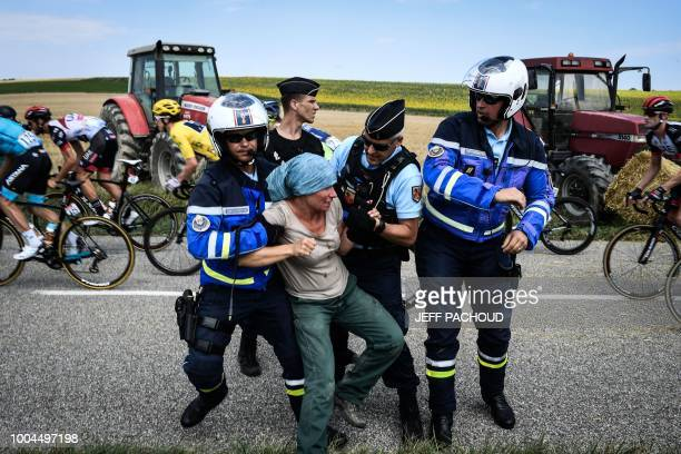 TOPSHOT Gendarmes detain a protester as Great Britain's Geraint Thomas wearing the overall leader's yellow jersey and the pack ride behind during a...