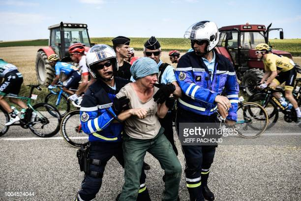 Gendarmes detain a protester as Great Britain's Geraint Thomas wearing the overall leader's yellow jersey and the pack ride behind during a farmers'...