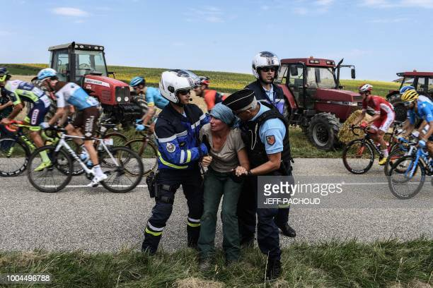 Gendarmes detain a protester as the pack rides behind during a farmers' protest who attempted to block the stage's route during the 16th stage of the...