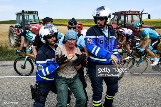 Gendarmes detain a protesting farmer as the pack rides behind during the 16th stage of the 105th edition of the Tour de France cycling race between...