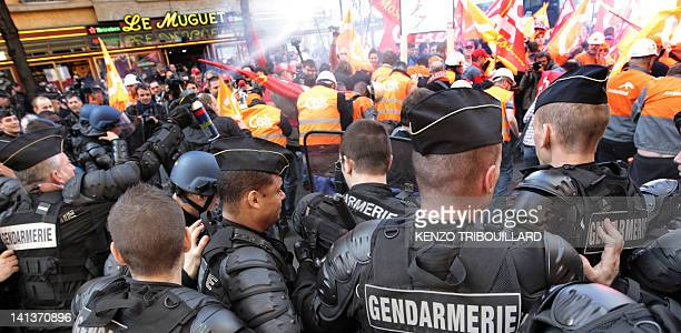 Gendarmes face workers of the ArcelorMittal plant of the company's steel production site in Florange demonstrating on March 15, 2012 in Paris, on...