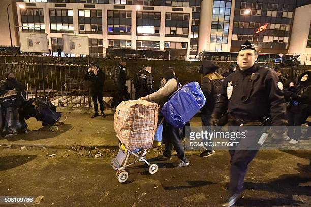 Gendarmes monitor the evacuation of a Roma migrants' camp deemed insecure and unsanitary on former railway tracks along Boulevard Ney in northern...