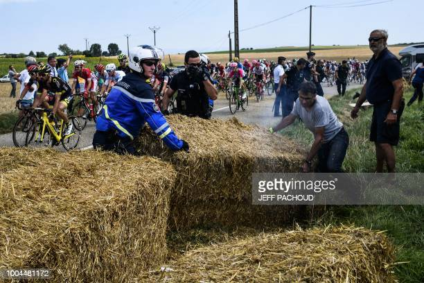 Gendarmes remove haystacks that were placed on the stage's route during a farmers' protest who attempted to block the race during the 16th stage of...