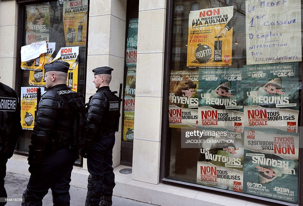 Gendarmes secure the area outside France's MEDEF employers' association headquarters on March 28, 2013 in Paris, while employees of French auto giant PSA Peugeot Citroen Aulnay are gathered to protest against the planned closure of their plant. At right on windows are pictured posters of French CGT trade union reading (from LtoR, up to down) 'No to the closure of PSA Aulnay', 'heads of MEDEF and shareholders are hyenas, sharks and vultures'.