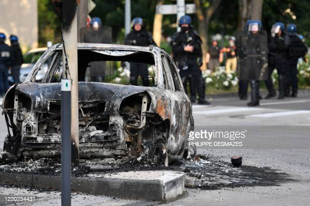 Gendarmes stand near a burnt car in the Gresilles area of Dijon, eastern France, on June 15 as new tensions flared in the city after it was rocked by...