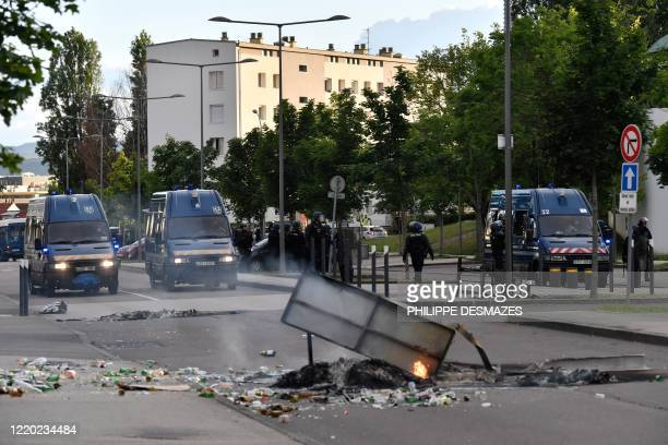 Gendarmes stand near their vehicles as burning trash in the street in the Gresilles area of Dijon, eastern France, on June 15 as new tensions flared...