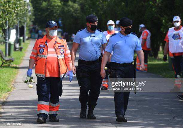 Gendarmes walk among ambulance workers during a protest in front of the Romanian Parliament in Bucharest on June 10, 20202. - The National Trade...