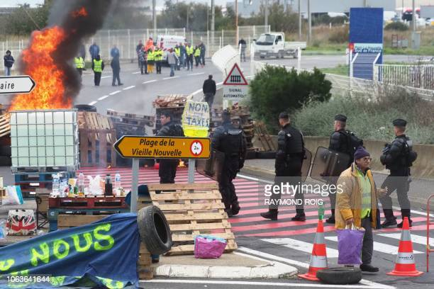 Gendarmes walk at a burning barricade as they disperse Yellow Vest protesters blocking the fuel depot of Port-La-Nouvelle, eastern France, on...