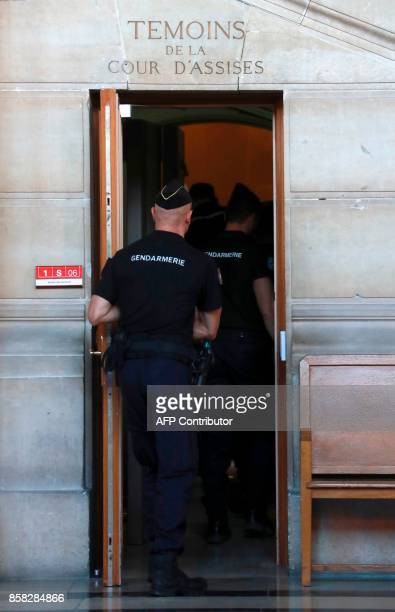Gendarmes walk through a door dedicated to the witnesses at Paris courthouse during the trial of Abdelkader Merah accused of helping his jihadist...
