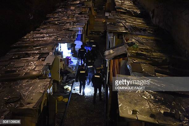 TOPSHOT Gendarmes walk through makeshift shacks during the evacuation of a Roma migrants' camp deemed insecure and unsanitary on former railway...