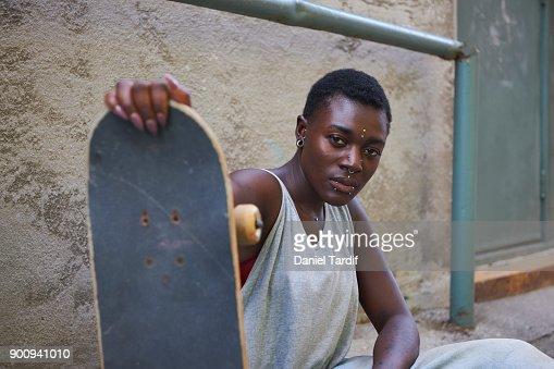 Gender fluid woman holding skateboard