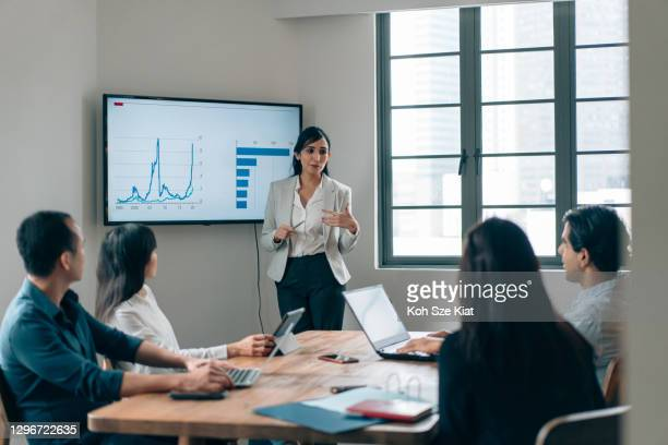 gender stereotype - female leadership in a small business meeting - economy stock pictures, royalty-free photos & images