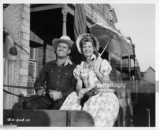 Gene Autry and Gail Davis sharing a carriage ride in a scene from the film 'Goldtown Ghost Riders' 1953