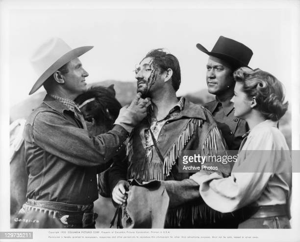Gene Autry examines Pat Buttram's wound while Kirby Grant and Gail Davis look on in a scene from the film 'Indian Territory' 1950