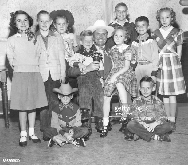 WINNERS— Gene Autry film cowboy and star of the Rocky Mountain Empire rodeo poses with the ten winners of the KLZ radio contest for the best...