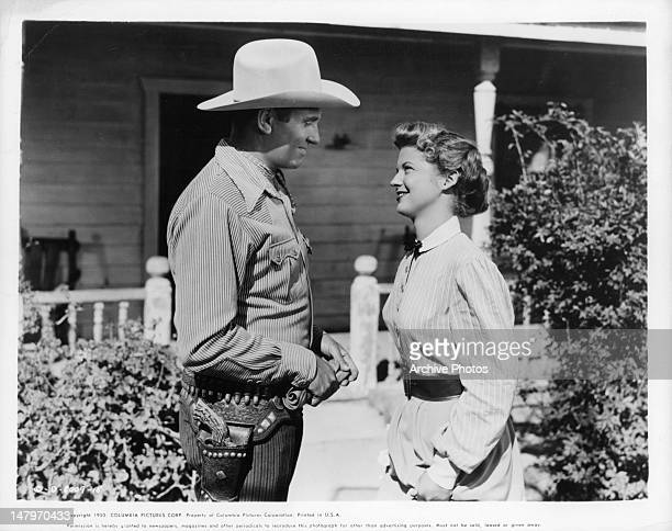 Gene Autry looking into the eyes of Gail Davis in a scene from the film 'Texans Never Cry' 1951