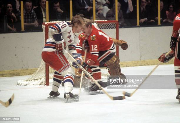 Gene Carr of the New York Rangers skates with the puck as he is defended by Pat Stapleton of the Chicago Blackhawks circa 1972 at the Madison Square...